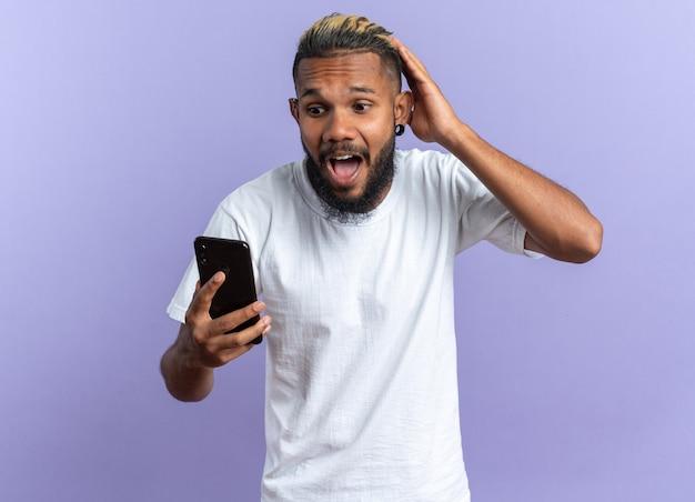 Afroamerikanischer junger mann im weißen t-shirt, der smartphone hält und es mit der hand auf dem kopf schockiert, die über blauem hintergrund steht