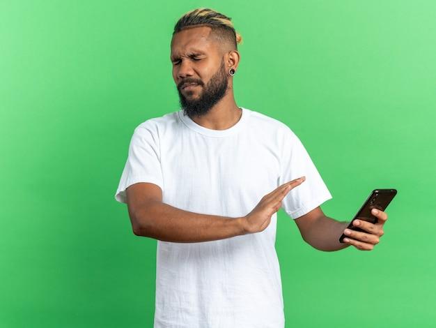 Afroamerikanischer junger mann im weißen t-shirt, der smartphone hält und verteidigungsgeste mit angewidertem ausdruck macht, der besorgt über grünem hintergrund steht