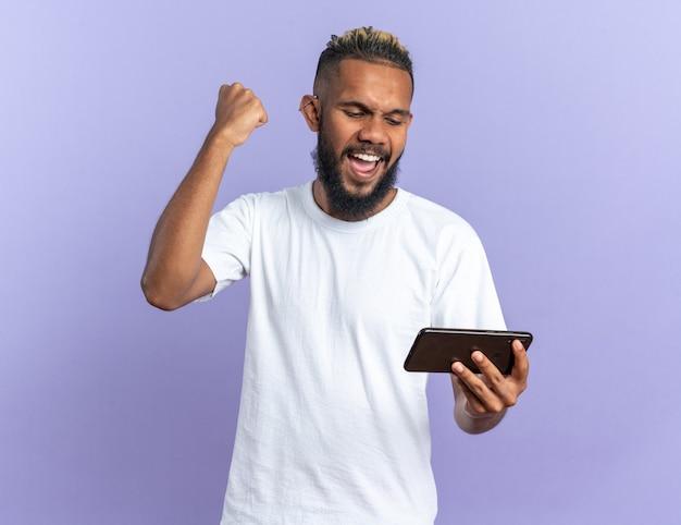 Afroamerikanischer junger mann im weißen t-shirt, der smartphone mit geballter faust glücklich und aufgeregt schreiend hält und sich über seinen erfolg freut, der auf blauem hintergrund steht