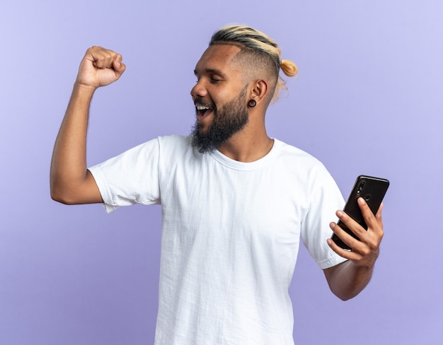 Afroamerikanischer junger mann im weißen t-shirt, der smartphone mit geballter faust glücklich und aufgeregt schreit und sich über seinen erfolg freut