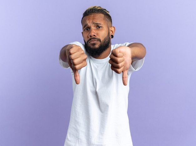 Afroamerikanischer junger mann im weißen t-shirt, der unzufrieden in die kamera schaut und daumen nach unten auf blauem hintergrund zeigt