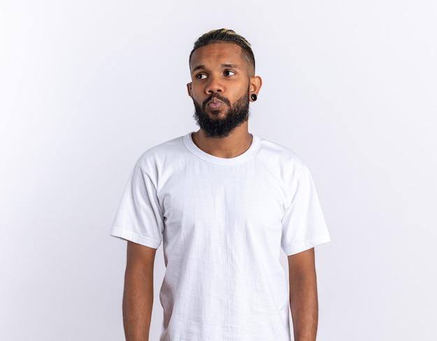 Afroamerikanischer junger mann im weißen t-shirt, der verwirrt beiseite schaut, stehend über weißem hintergrund