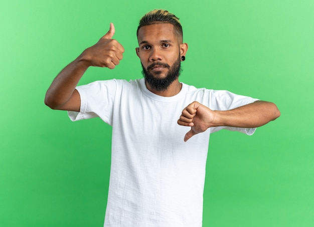 Afroamerikanischer junger mann im weißen t-shirt, der verwirrt in die kamera schaut und daumen hoch zeigt Kostenlose Fotos