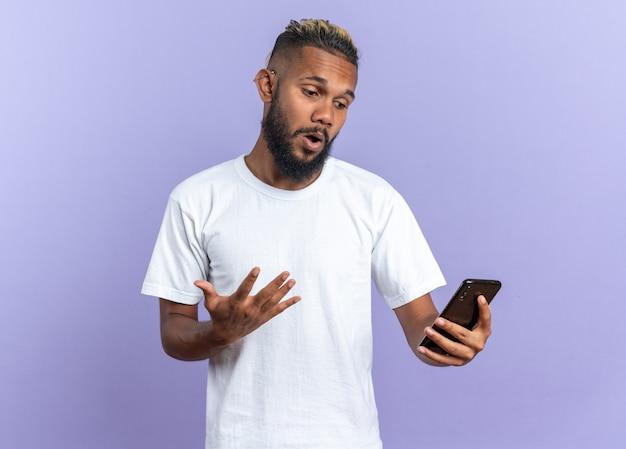 Afroamerikanischer junger mann im weißen t-shirt mit blick auf den bildschirm seines smartphones
