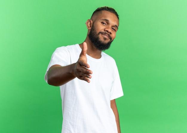Afroamerikanischer junger mann im weißen t-shirt mit blick in die kamera lächelt freundlich und bietet handgruß auf grünem hintergrund an