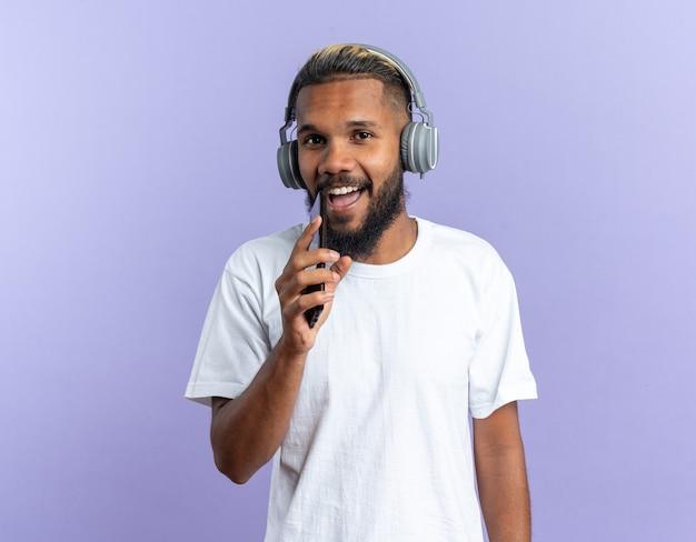 Afroamerikanischer junger mann im weißen t-shirt mit kopfhörern, die smartphone halten und als mikrofon singen, fröhlich und fröhlich