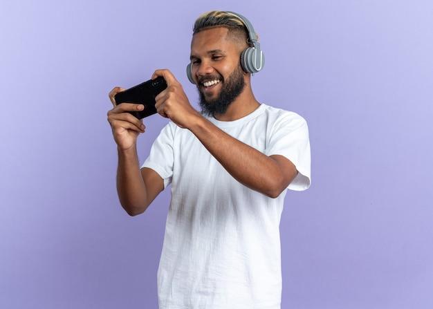 Afroamerikanischer junger mann im weißen t-shirt mit kopfhörern, die spiele mit smartphone spielen, glücklich und aufgeregt