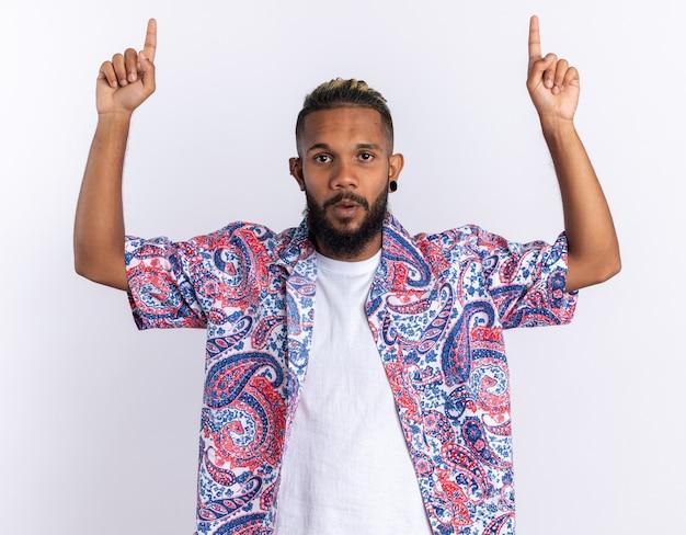 Afroamerikanischer junger mann in buntem hemd, der erstaunt und überrascht in die kamera schaut und mit den zeigefingern nach oben auf weißem hintergrund zeigt