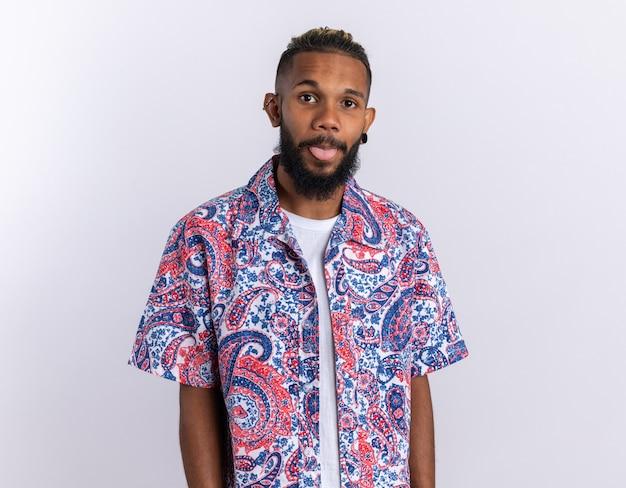 Afroamerikanischer junger mann in buntem hemd, der glücklich und positiv in die kamera schaut und die zunge herausstreckt
