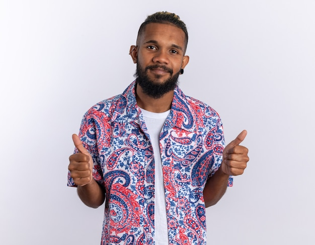 Afroamerikanischer junger mann in buntem hemd, der in die kamera schaut und fröhlich lächelt