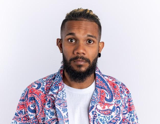 Afroamerikanischer junger mann in buntem hemd, der verwirrt in die kamera schaut, stehend über weißem hintergrund