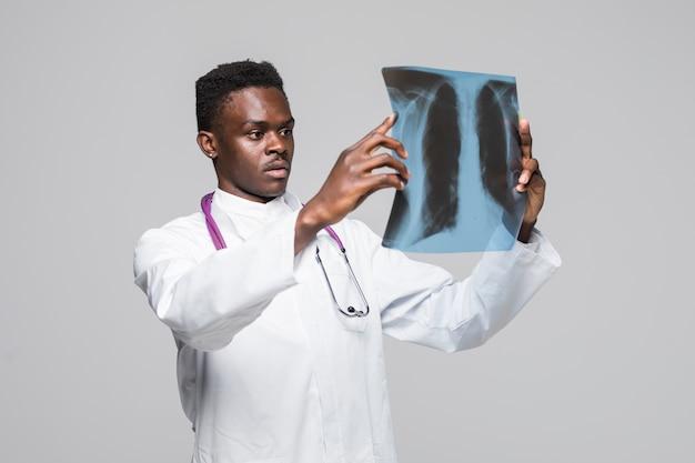 Afroamerikanischer junger medizinischer arzt, der röntgenstrahl lokalisiert auf grauem hintergrund betrachtet