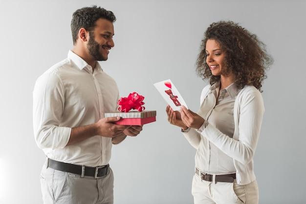 Afroamerikanischer kerl hält eine geschenkbox