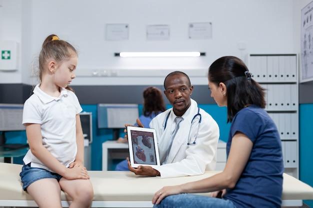 Afroamerikanischer kinderarzt, der tablet-computer mit herzradiographie hält