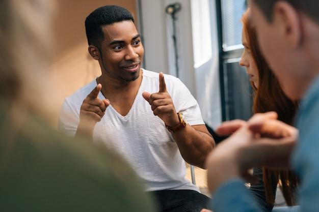 Afroamerikanischer männlicher führer, der dem jungen kreativen geschäftsteam während des brainstormings im besprechungsraum neue strategien erklärt. geschäftsmann, der arbeit mit team im sitzungssaal bespricht.