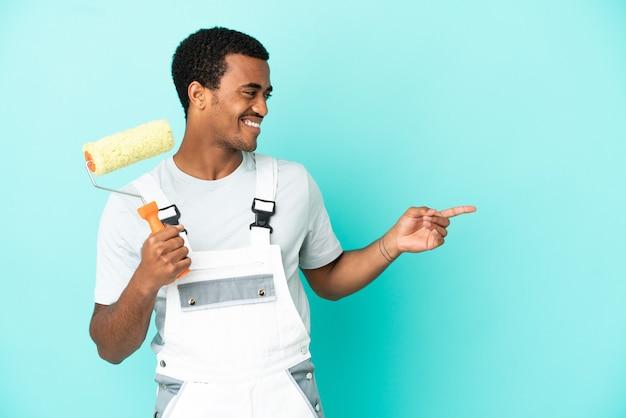 Afroamerikanischer malermann über isoliertem blauem hintergrund, der mit dem finger zur seite zeigt und ein produkt präsentiert