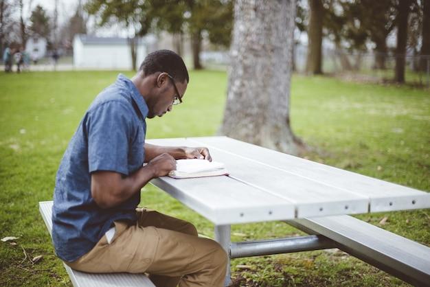 Afroamerikanischer mann, der an einem tisch sitzt und die bibel liest