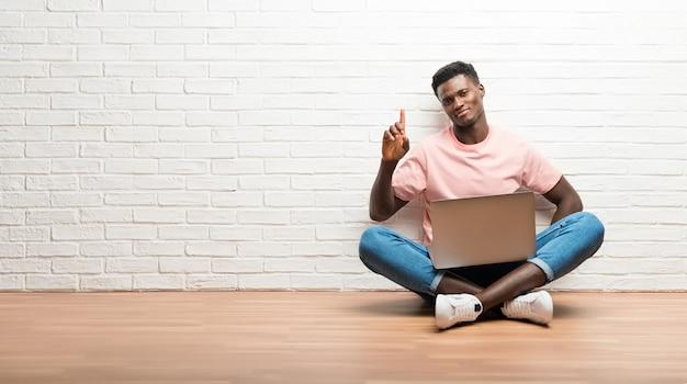 Afroamerikanischer mann, der auf dem boden mit seinem laptop zählt zeichen der nr. eine sitzt