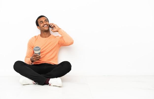 Afroamerikanischer mann, der auf dem boden über isoliertem copyspace-hintergrund sitzt und kaffee zum mitnehmen und ein handy hält