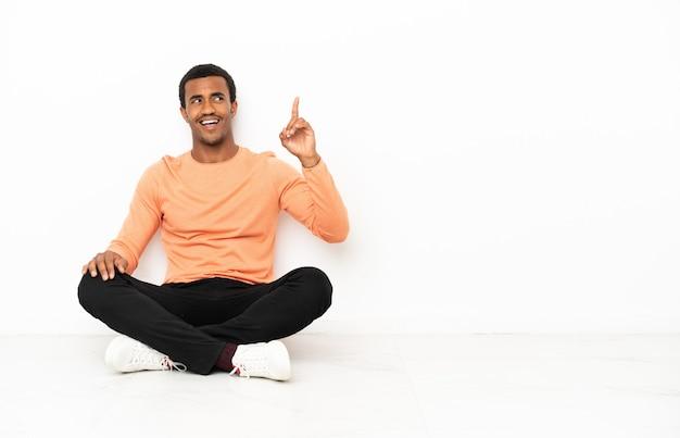Afroamerikanischer mann, der auf dem boden über isoliertem hintergrund sitzt und beabsichtigt, die lösung zu realisieren, während er einen finger hochhebt