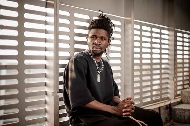 Afroamerikanischer mann, der auf dem fensterbrett sitzt