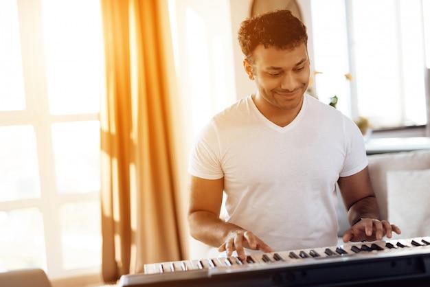 Afroamerikanischer mann, der auf synthesizer und dem unterzeichnen spielt
