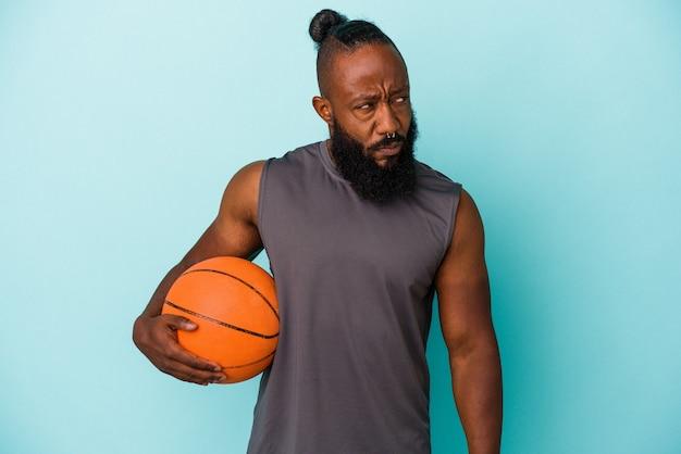 Afroamerikanischer mann, der basketball einzeln auf blauem hintergrund spielt, verwirrt, fühlt sich zweifelhaft und unsicher.