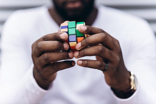 Afroamerikanischer mann, der beiläufige kleidung in der modernen stadt trägt, die farbiges puzzlespiel sammelt, nahaufnahmefoto