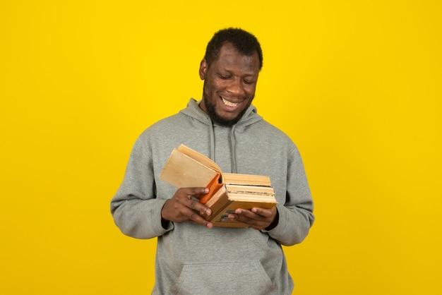 Afroamerikanischer mann, der bücher in seiner hand liest, steht über gelber wand.