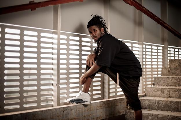 Afroamerikanischer mann, der das angehobene bein hält