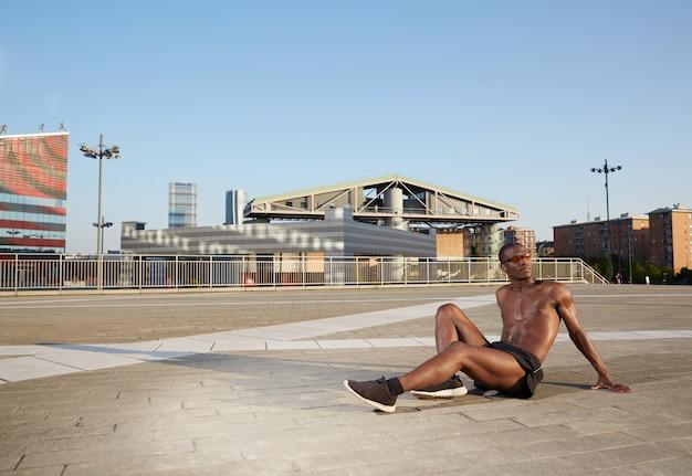 Afroamerikanischer mann, der das ausdehnen in städtische umwelt tut