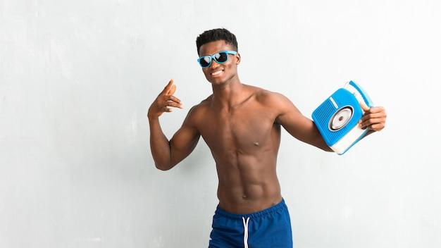 Afroamerikanischer mann, der die sommerferien halten weinleseradio genießt
