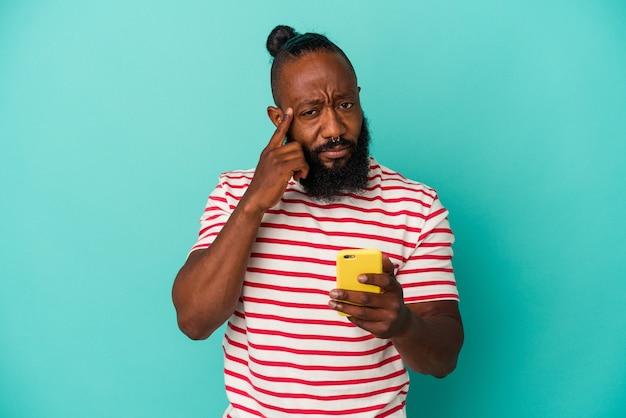 Afroamerikanischer mann, der ein mobiltelefon isoliert auf blauem hintergrund hält und mit dem finger auf den tempel zeigt, denkt, konzentriert sich auf eine aufgabe.