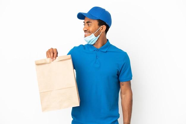 Afroamerikanischer mann, der eine tüte essen zum mitnehmen auf weißem hintergrund mit seitenblick isoliert