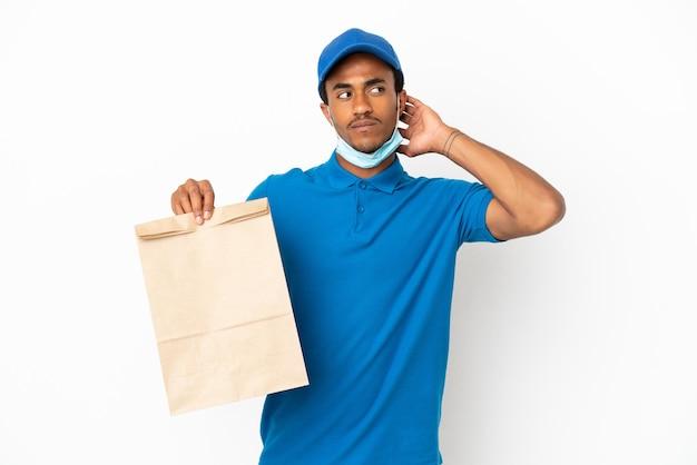 Afroamerikanischer mann, der eine tüte essen zum mitnehmen isoliert auf weißem hintergrund mit zweifeln nimmt