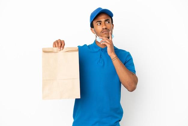 Afroamerikanischer mann, der eine tüte essen zum mitnehmen isoliert auf weißem hintergrund nimmt und beim nachschlagen zweifel hat