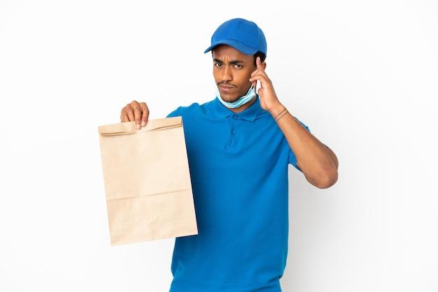 Afroamerikanischer mann, der eine tüte essen zum mitnehmen isoliert auf weißem hintergrund nimmt und eine idee denkt
