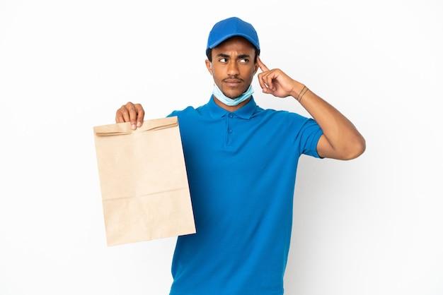 Afroamerikanischer mann, der eine tüte essen zum mitnehmen isoliert auf weißem hintergrund nimmt und zweifel hat und denkt?