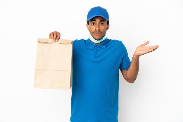 Afroamerikanischer mann, der eine tüte essen zum mitnehmen isoliert auf weißem hintergrund nimmt und zweifel hat, während er die hände hebt