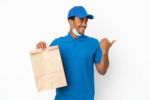 Afroamerikanischer mann, der eine tüte essen zum mitnehmen nimmt, isoliert auf weißem hintergrund, der auf die seite zeigt, um ein produkt zu präsentieren
