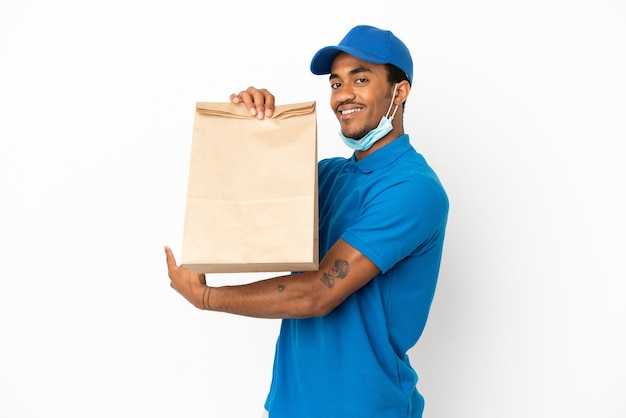 Afroamerikanischer mann, der eine tüte essen zum mitnehmen nimmt, isoliert auf weißem hintergrund, der nach hinten zeigt
