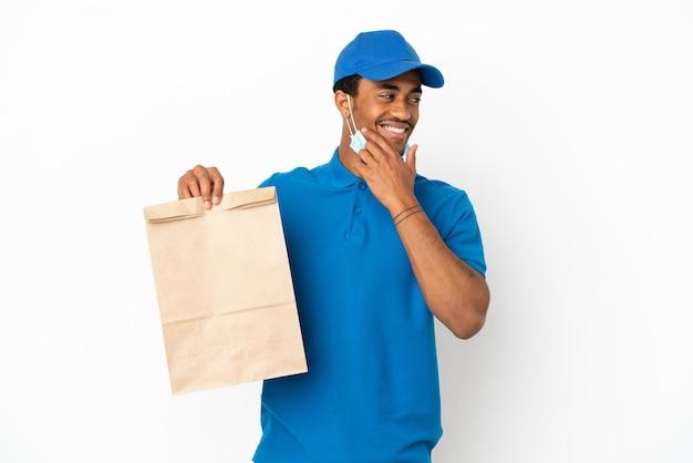 Afroamerikanischer mann, der eine tüte essen zum mitnehmen nimmt, isoliert auf weißem hintergrund, der zur seite schaut und lächelt
