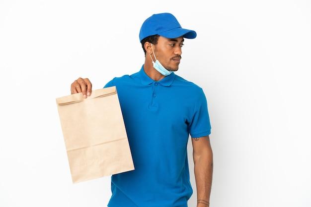 Afroamerikanischer mann, der eine tüte essen zum mitnehmen nimmt, isoliert auf weißem hintergrund, der zur seite schaut