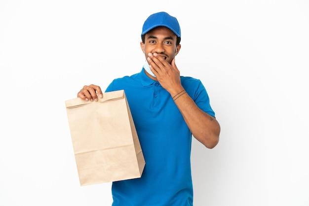 Afroamerikanischer mann, der eine tüte essen zum mitnehmen nimmt, isoliert auf weißem hintergrund, glücklich und lächelnd, den mund mit der hand bedeckend