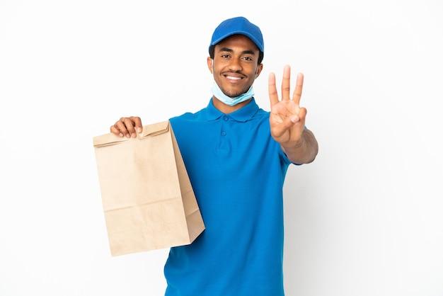 Afroamerikanischer mann, der eine tüte essen zum mitnehmen nimmt, isoliert auf weißem hintergrund, glücklich und zählt drei mit den fingern