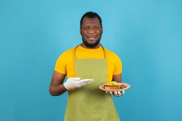 Afroamerikanischer mann, der einen teller mit essen in der hand hält, steht über blauer wand.