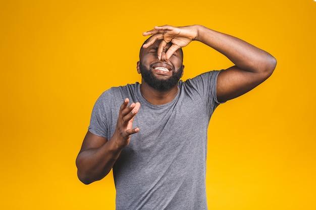 Afroamerikanischer mann, der etwas stinkendes und ekelhaftes, unerträgliches riecht, atem mit den fingern auf der nase haltend. schlechtes geruchskonzept.