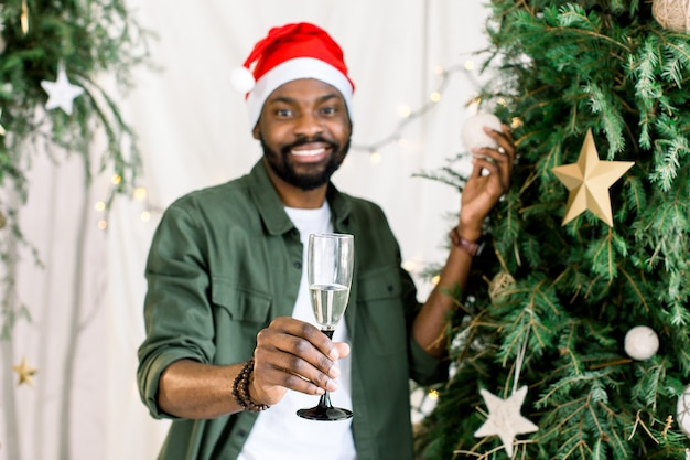 Afroamerikanischer mann, der glas mit champagner nahe weihnachtsbaum hält