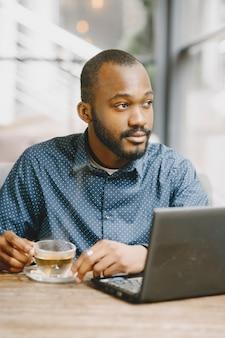 Afroamerikanischer mann, der hinter einem laptop arbeitet. mann mit bart sitzt in einem café und trinkt einen tee.