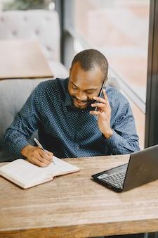 Afroamerikanischer mann, der hinter einem laptop arbeitet und am telefon spricht. mann mit bart sitzt in einem café.